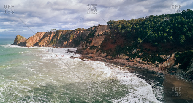 Aerial view of the rocky shore and a wild beach in Asturias, Spain