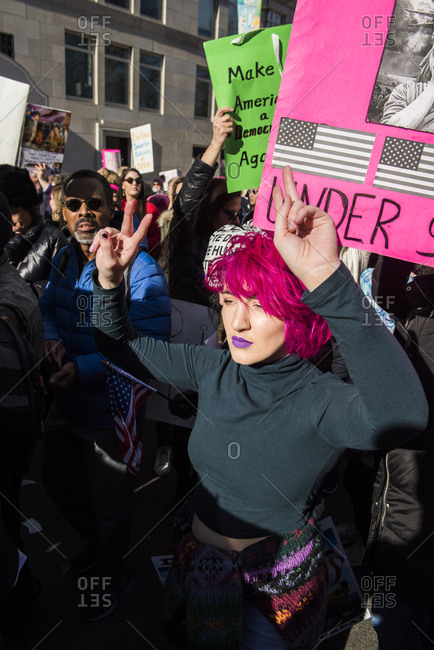 New York City, New York, USA - January 20, 2018: Woman with pink hair making peace signs at Women's March