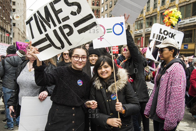 New York City, New York, USA - January 20, 2018: Young women holding signs in front of crowd at Women's March