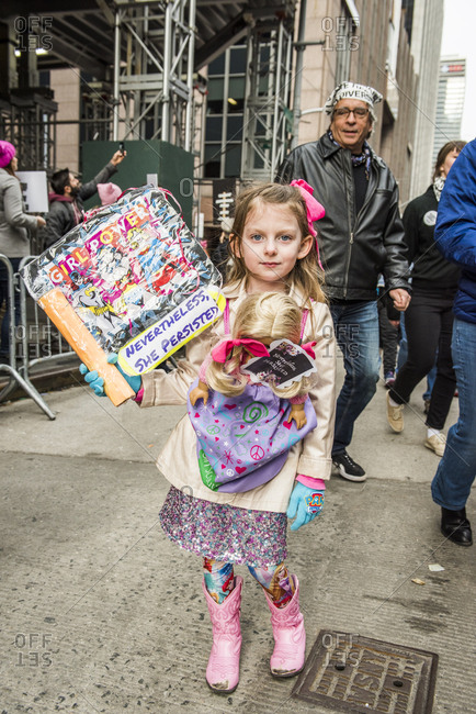New York City, New York, USA - January 20, 2018: Girl holding sign and carrying doll at Women's March
