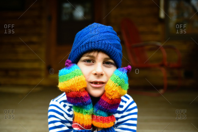 Boy wearing rainbow colored mittens