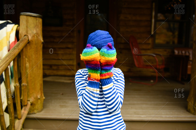 Child wearing rainbow colored mittens