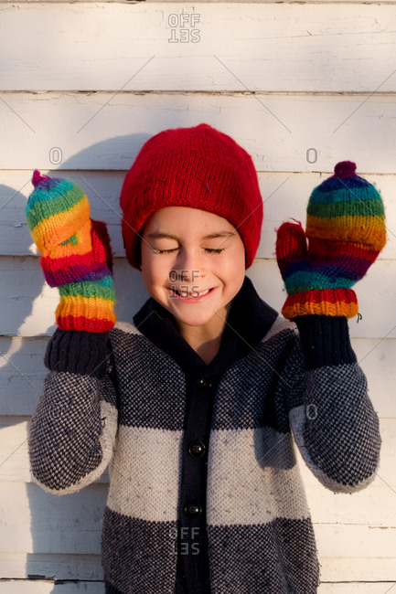 Boy wearing rainbow mittens and red hat