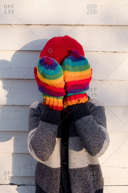 Boy covering face with rainbow mittens