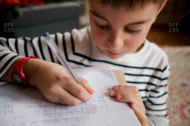Close up of a school aged boy learning to write