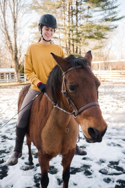 Teen girl riding a brown horse
