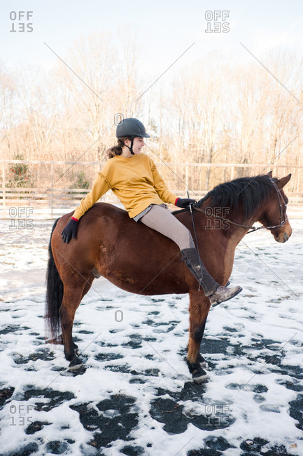 Teenage girl riding a brown horse