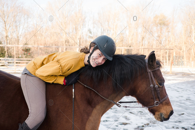 Portrait of a teen girl riding a brown horse