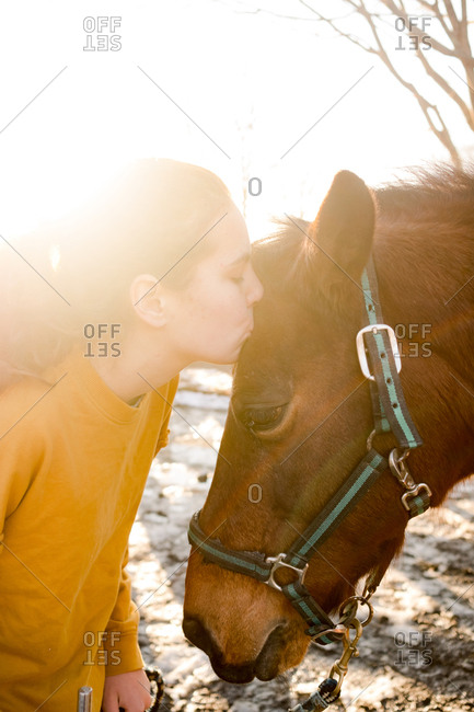 Teenage girl kissing a brown horse