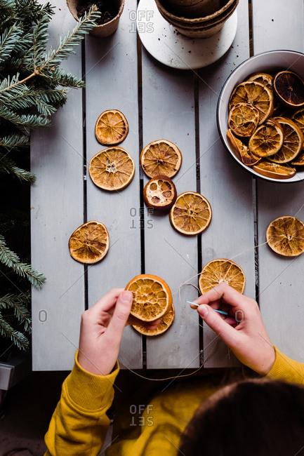 Teen girl creating an orange garland for Christmas tree