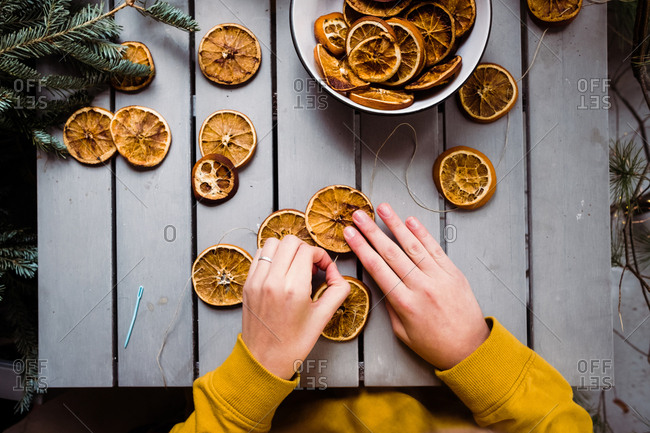 Teen girl threading orange sliced into garland
