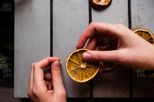 Close up of teen girl creating an orange garland