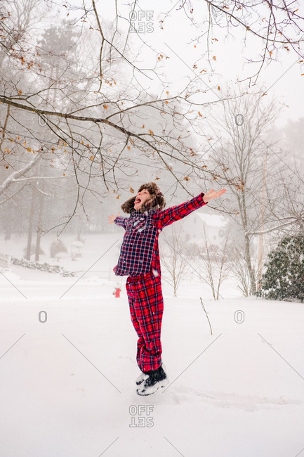 Boy in the snow in pajamas and hat