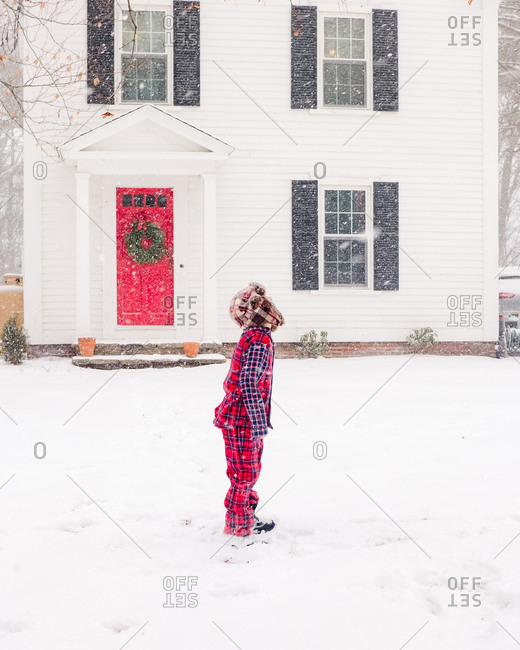 Boy catching snowflakes in the snow in pajamas and hat
