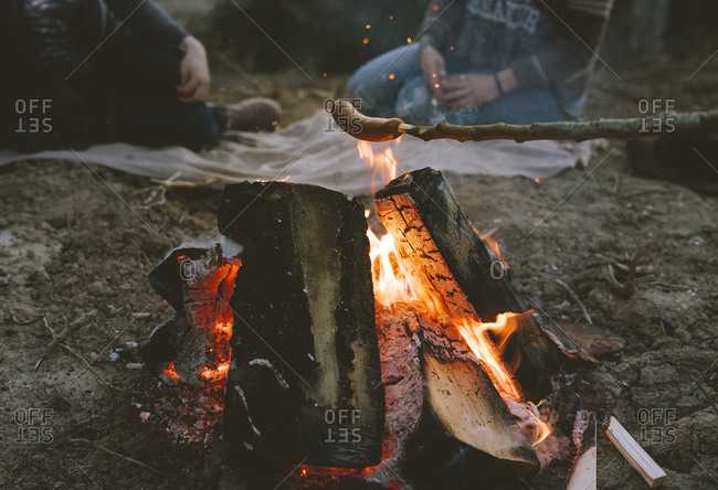 Hot dog cooking over campfire with friends on blanket in background