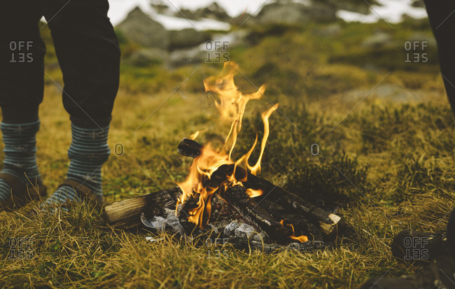 Two sets of feet stand besides a small campfire
