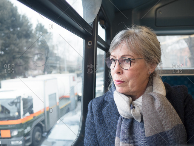 Middle aged woman sitting on the bus looking out of the window