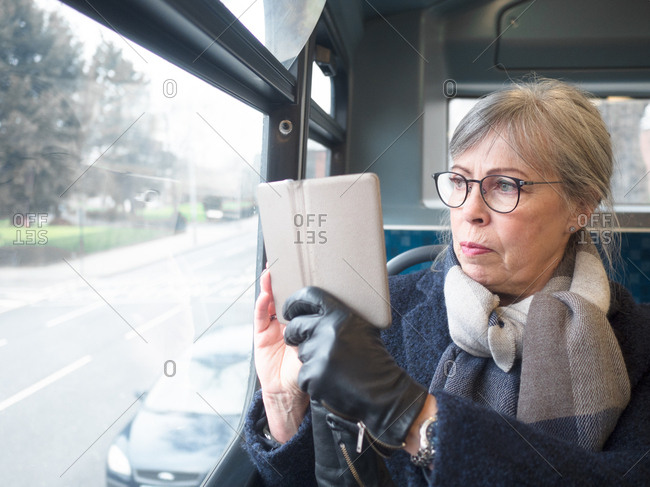Middle aged woman sitting on the bus taking photo with smartphone