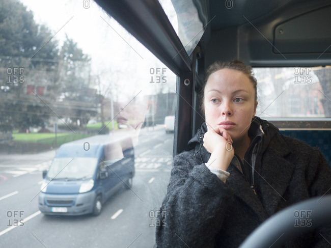 Young woman sitting on the bus looking out of the window