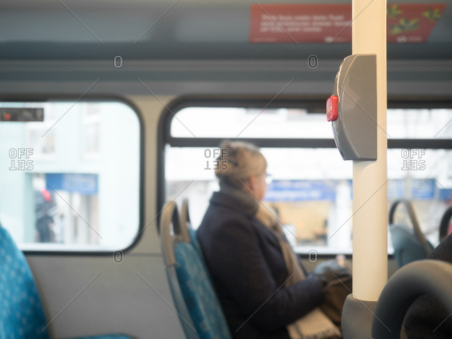 Woman looking out of bus window with stop button in the foreground