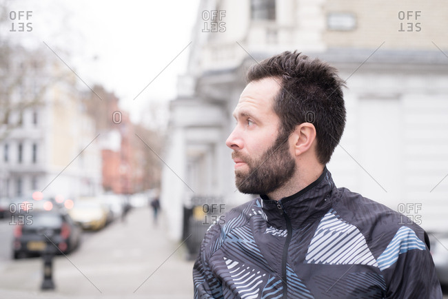 Profile view of runner waiting on street corner on cold winter morning
