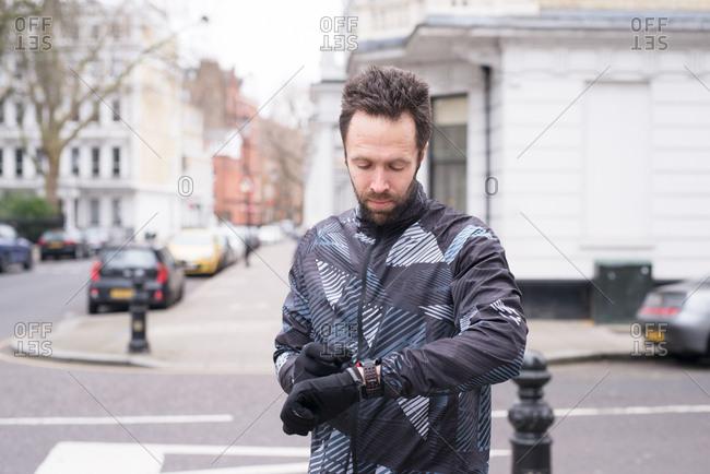 Runner checking activity tracker on cold winter morning