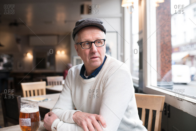 Middle aged man looks out of the window while enjoying a glass of beer