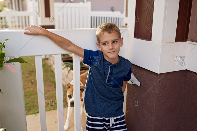 Blonde boy leaning on white gate with dog in background