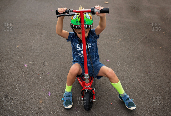 Boy wearing a spiky helmet and sitting on a scooter