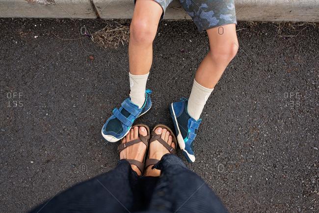 Adult feet on pavement beside child's feet