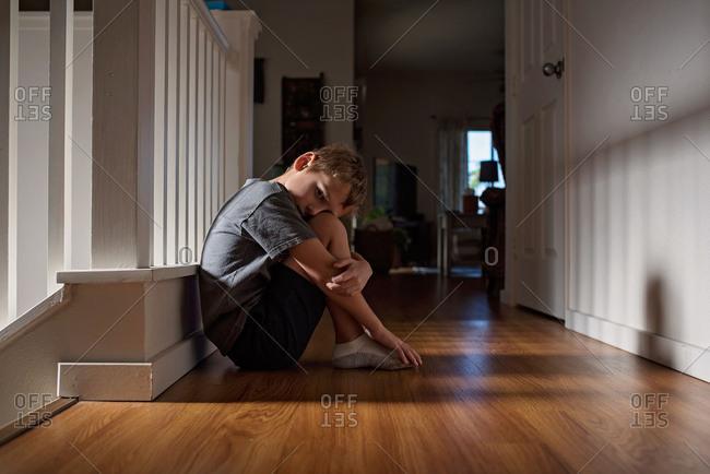 Upset boy sitting on hallway floor