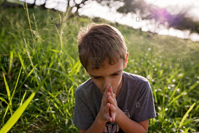 Boy blowing on a blade of grass
