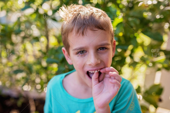 Boy wiggling his loose tooth