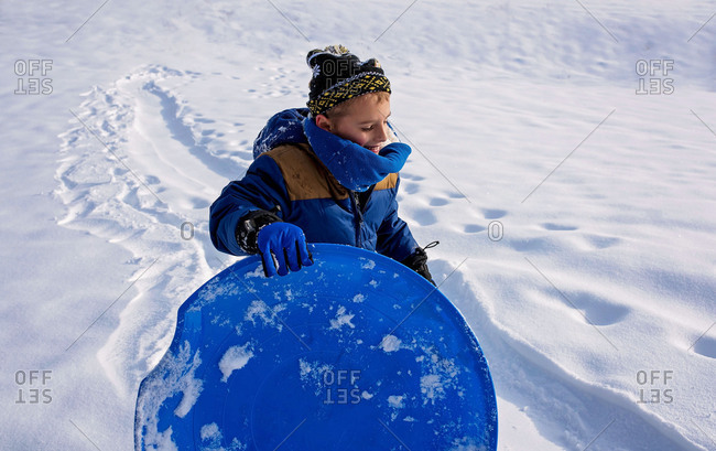 Young boy in the snow with a blue sled