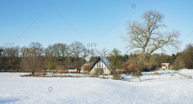 Remote home in rural snowy landscape with blue sky