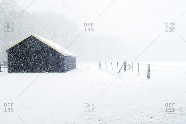 Small black wooden barn in snowy countryside during snowfall
