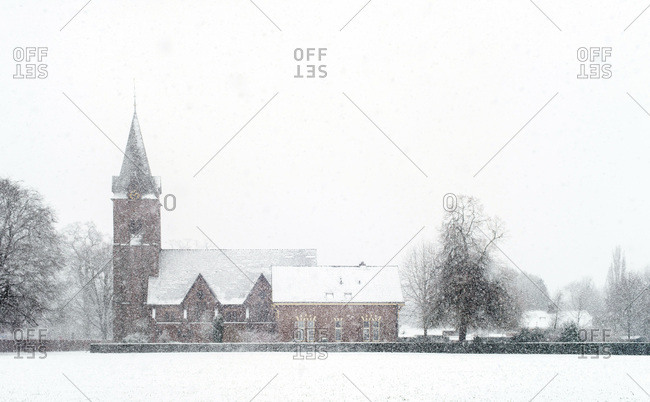 Church in rural landscape covered in snow during snowfall