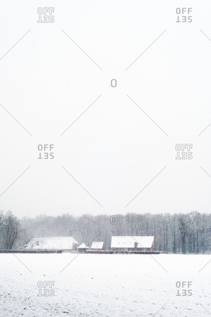 Old Dutch farm covered in snow during snowfall
