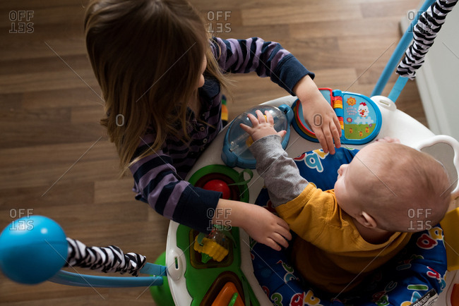 Toddler playing with baby brother in his bouncer