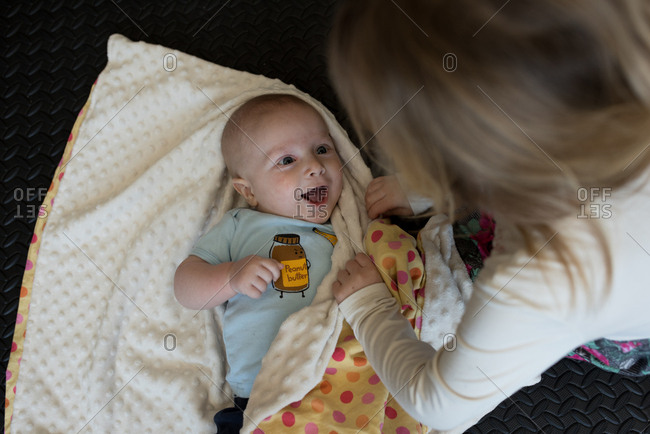 Happy baby boy looking up at sister