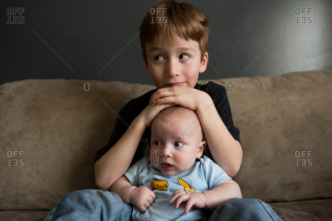 Portrait of boy sitting with baby brother