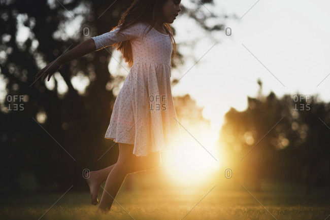Tween girl playing in field at sunset
