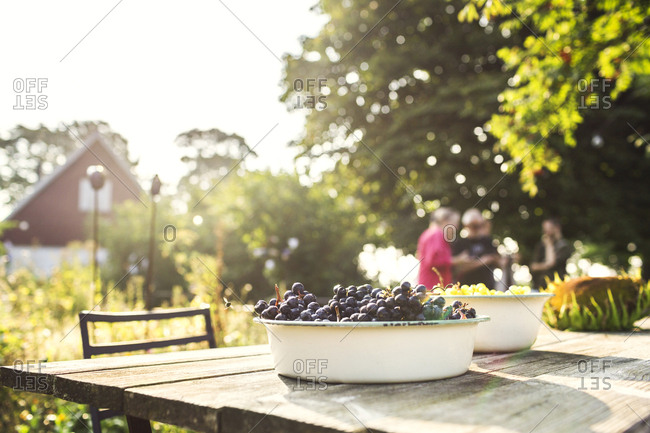 Red grapes in bowl on wooden table