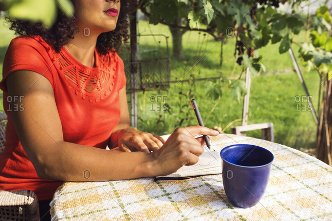 Mid section of woman taking notes on table in vineyard