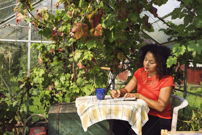 Woman taking notes on table in vineyard