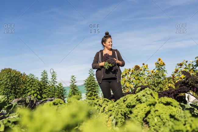 Woman holding kale in field