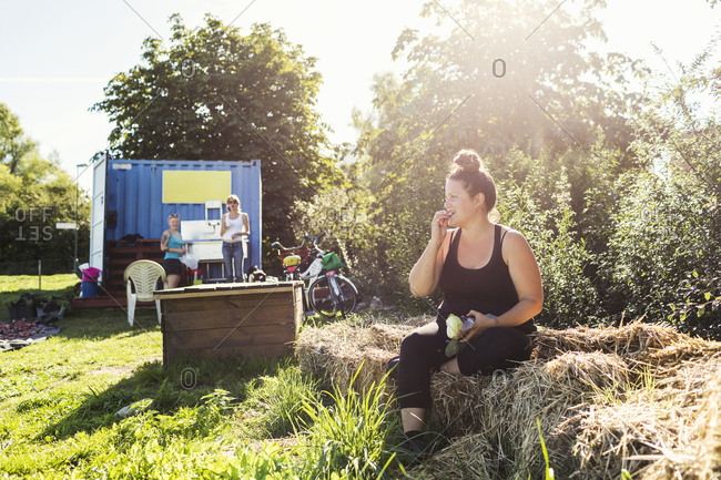 Woman sitting on hay bale and eating apple
