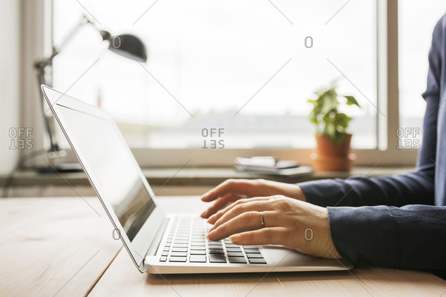 Woman using laptop on wooden table