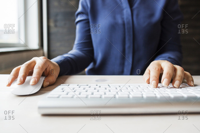 Woman using computer keyboard and mouse
