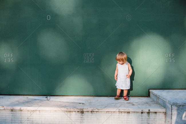 Small girl standing alone outside